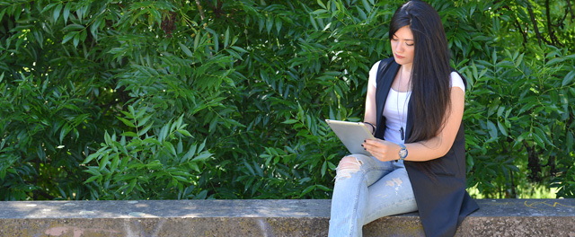 Girl reading on a tablet on Campus